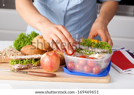 Woman in blue t-shirt preparing a lunchbox in the kitchen - stock photo