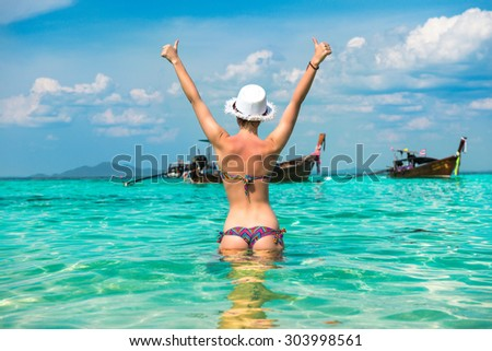 Woman in bright bikini standing in the water with thumbs up - stock photo