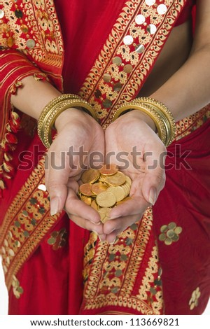 Woman in bright red mekhla holding gold coins - stock photo