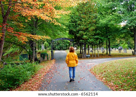 Woman in bright yellow jacket walking in Fall foliage