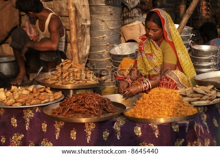 Woman in brightly colored sari selling indian sweets from a market stall. - stock photo