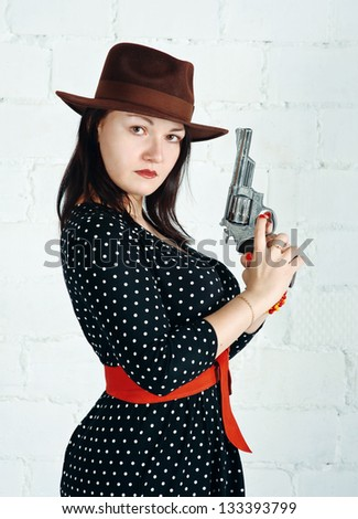 Woman in brown hat with gun - stock photo
