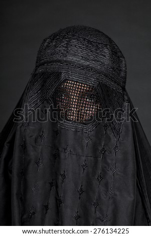 Woman in burka isolated on black close