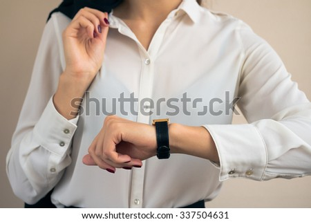 Woman in business attire looking the time on hand watch closeup - stock photo