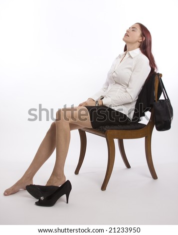 Woman in business attire sitting back with shoes off relaxing - stock photo