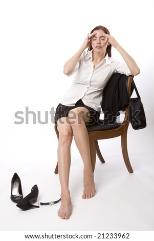 Woman in business attire sitting on a chair and holding her head - stock photo