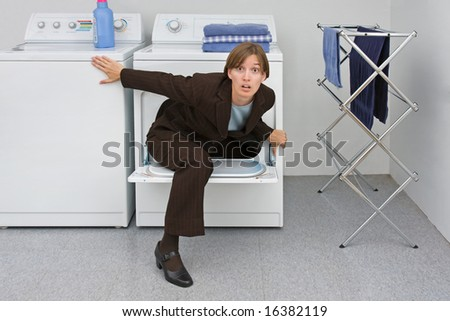 Woman in business suit climbs out of a clothes dryer. Metaphor for the emergence of women and mothers into the business world. - stock photo