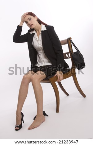 Woman in business suit holding her head and looking exhausted