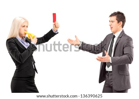 Woman in business suit showing a red card and blowing a whistle to a man in a business suit, isolated on white background - stock photo