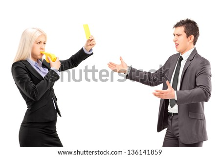 Woman in business suit showing a yellow card and blowing a whistle to a man in a business suit, isolated on white background - stock photo