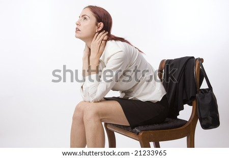 Woman in business suit sitting on chair looking sad and tired - stock photo