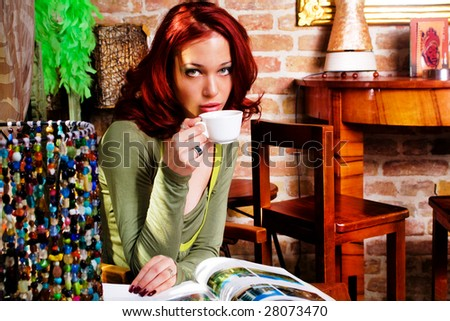 woman in cafe drinking coffee and reading magazine - stock photo