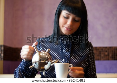 woman in cafe filling cup with teapot - stock photo