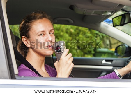 Woman in car blowing into breathalyzer - stock photo