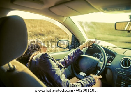 woman in car indoor keeps wheel. Head lie on window. Young adult girl relaxing, enjoying nice day, sunny weather, hot sunset in wheat field. Resting after hard working