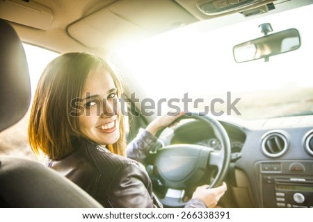 woman in car indoor keeps wheel turning around smiling looking at passengers in back seat idea taxi driver against sunset rays Light shine sky Concept of exam Vehicle - second home the girl - stock photo