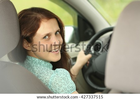 woman in car indoor keeps wheel turning around smiling looking at passengers in back seat idea taxi driver against sunset rays Light shine sky. Concept of exam Vehicle - second home the girl