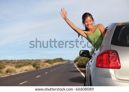 Woman in car road trip waving out the window smiling.  Image from Teide, Tenerife. Mixed race Asian / Caucasian woman.
