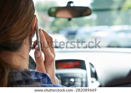 Woman In Car Talking On Mobile Phone Whilst Driving - stock photo