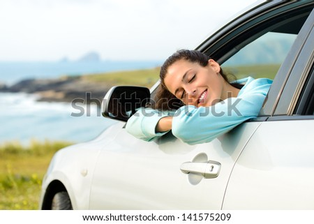 Woman in car travel relaxing and enjoying peace and silence of beautiful summer coast nature landscape. Happy girl traveling. - stock photo