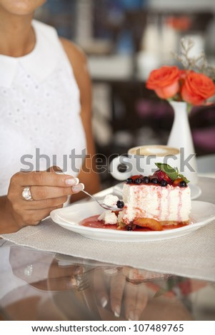 Woman in care with Dessert - Cheesecake with Berries Sauce Green Mint and coffee cup. Piece of delicious high-calorie cake with strawberry vanilla cream on plate and on table.unhealthy food.breakfast
