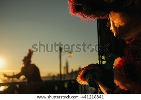 Woman in carnival costume looks at a man in morning lights hiding behind a door