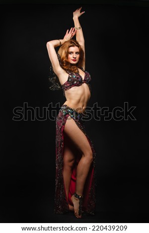 woman in carnival costume with a fan on black. belly dance - stock photo