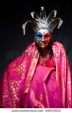 Woman in carnival dress and Venetian mask on a dark background