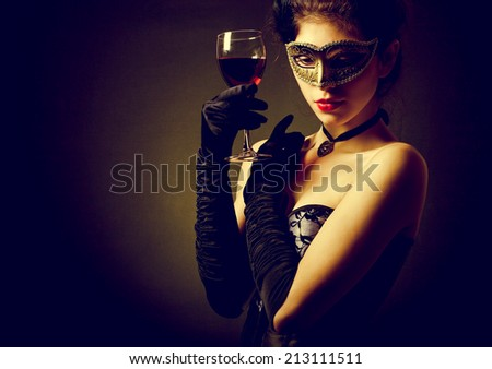woman in carnival mask and a glass of red wine. - stock photo