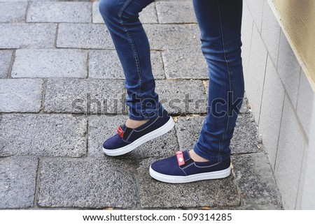 Woman in casual shoes in the city. Trendy fall outfit on rainy day. Stylish woman in comfortable blue suede moccasins and dark blue jeans walking on the wet pavement.