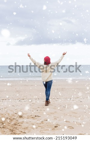 Woman in casual warm wear stretching arms on beach against snow falling - stock photo
