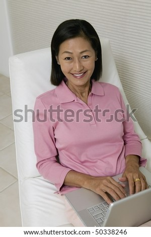 Woman in Chair Using Laptop, portrait, high angle view - stock photo