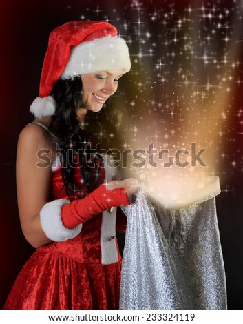 Woman  in christmas hat smiles and holding a gift in magic bag on a dark background - stock photo