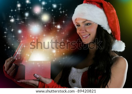 Woman  in christmas hat smiles and holding a gift in magic packing  on a dark background - stock photo