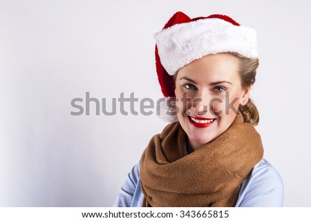 Woman in christmas hat smiling over white background.