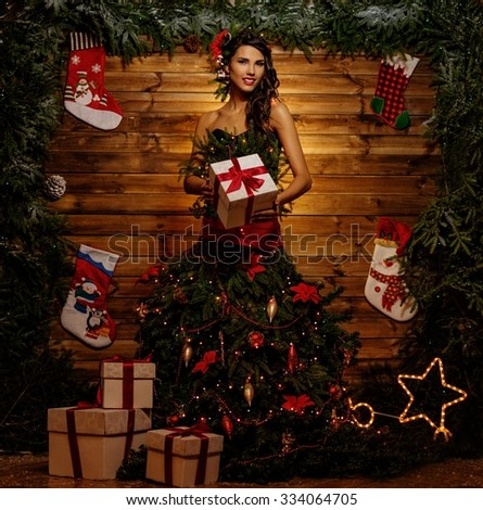 Woman in christmas tree dress in wooden interior with gift box - stock photo