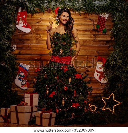 Woman in christmas tree dress in wooden interior with glass of champagne  - stock photo