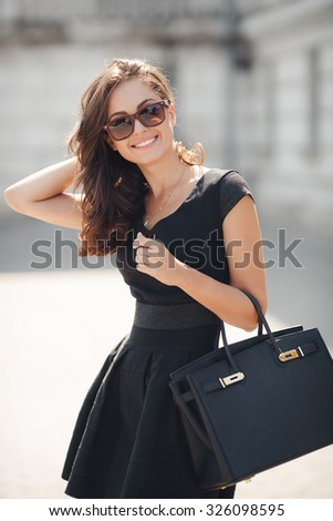 Woman in classic black dress, hills and bag sitting on stairs in the city street. woman portrait outdoor in summer - stock photo