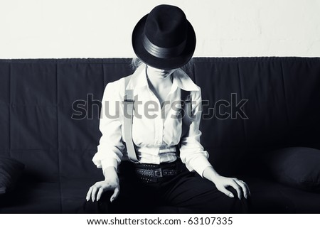 Woman in classic men's hat, and a shirt sitting on the sofa