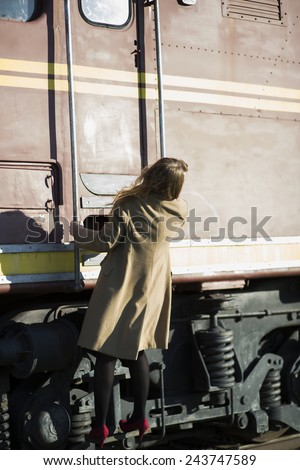 Woman in coat climbs the ladder at wagon - stock photo
