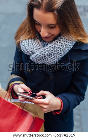 Woman in coat texting on mobile phone after shopping - stock photo