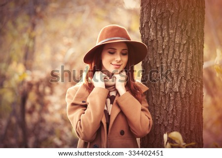 Woman in coat with hat and scarf holding cup in autumn park - stock photo