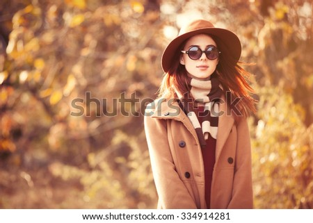 Woman in coat with hat and scarf in autumn park - stock photo