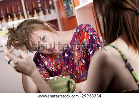 Woman in coffee house bored by female companion - stock photo