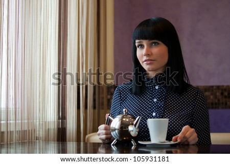 woman in coffee with teapot in hands - stock photo