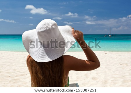 Woman in color hat sitting in chaise longue - stock photo