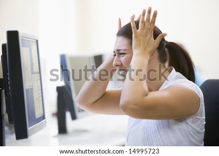 Woman in computer room looking frustrated - stock photo