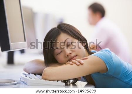 Woman in computer room sleeping - stock photo
