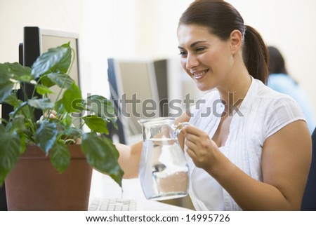 Woman in computer room watering plant smiling - stock photo