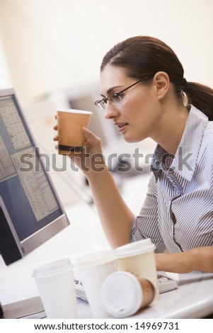 Woman in computer room with many cups of empty coffee around her - stock photo
